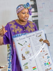 Mwalimu teaching with her African Foundation Timeline